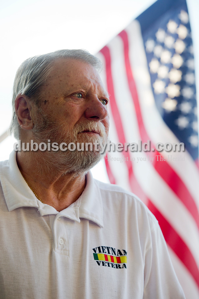 Rachel Mummey/The Herald<br /> Vietnam veteran Patrick O'Keefe stood in front of the American flag on display at his Jasper home Wednesday evening. O'Keefe served as a Sergeant in the United States Air Force and was stationed in Korat Royal Thai Air Force Base in Thailand from 1968-1969. O'Keefe said he found it gratifying to listen to comrades in Vietnam who heard F-4 and F-105 fighter jets fly overhead, letting them know there was support coming in.