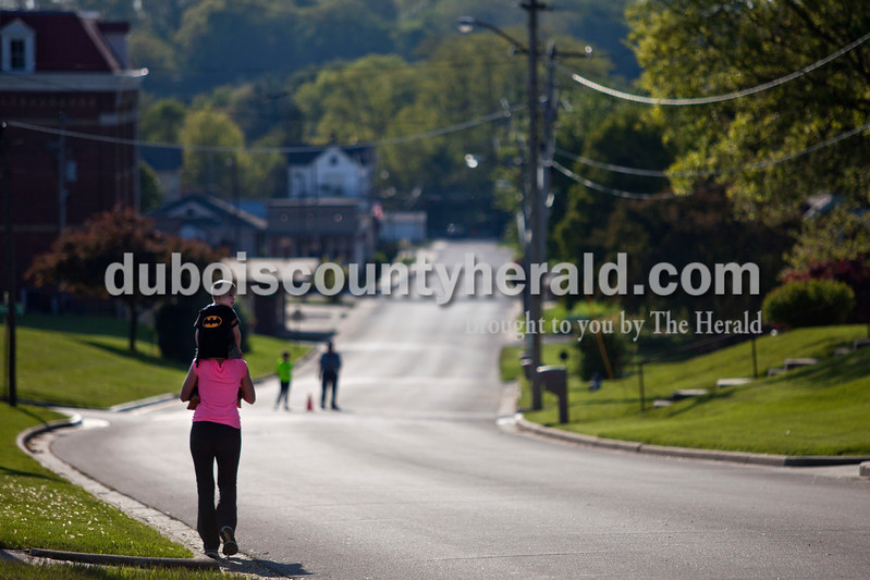 Audrey Meyer walked with her son Dexter, 4, both of St. Anthony during the 5K Fun Fest put on by Ferdinand Elementary School on Friday evening in Ferdinand. The festivities included a 5K run and walk, yoga, circuit training, a bouncy house and an obstacle course. <br /> Alisha Jucevic/The Herald