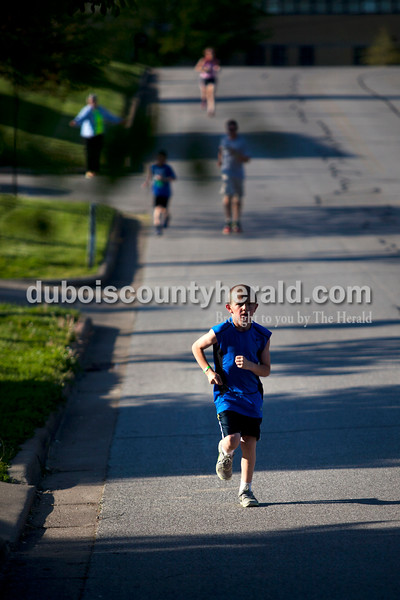"""Carter Giesler of Ferdinand, 8, ran along Alabama St. during the 5K Fun Fest put on by Ferdinand Elementary School on Friday evening in Ferdinand. The festivities included a 5K run and walk, yoga, circuit training, a bouncy house and an obstacle course. """"The wellness committee we have here is amazing,"""" said principal Stacy Kitchin. Last year the school put on a health fair and they wanted to try something new this year. <br /> <br /> <br /> Alisha Jucevic/The Herald"""