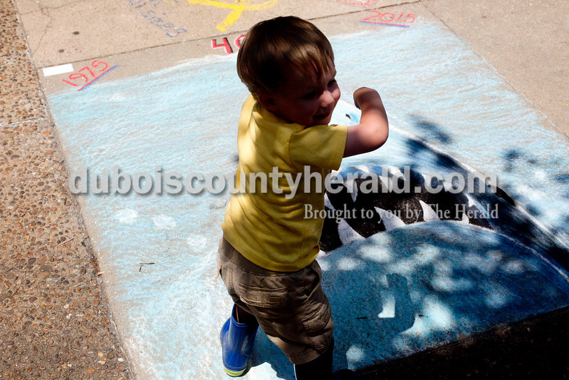 "Ariana van den Akker/The Herald<br /> Gavin Uebelhor of Jasper, 2, ""feeds"" leaves to a drawing of ""Jaws"" during the 12th annual Chalk Walk Arts festival in downtown Jasper on Saturday."