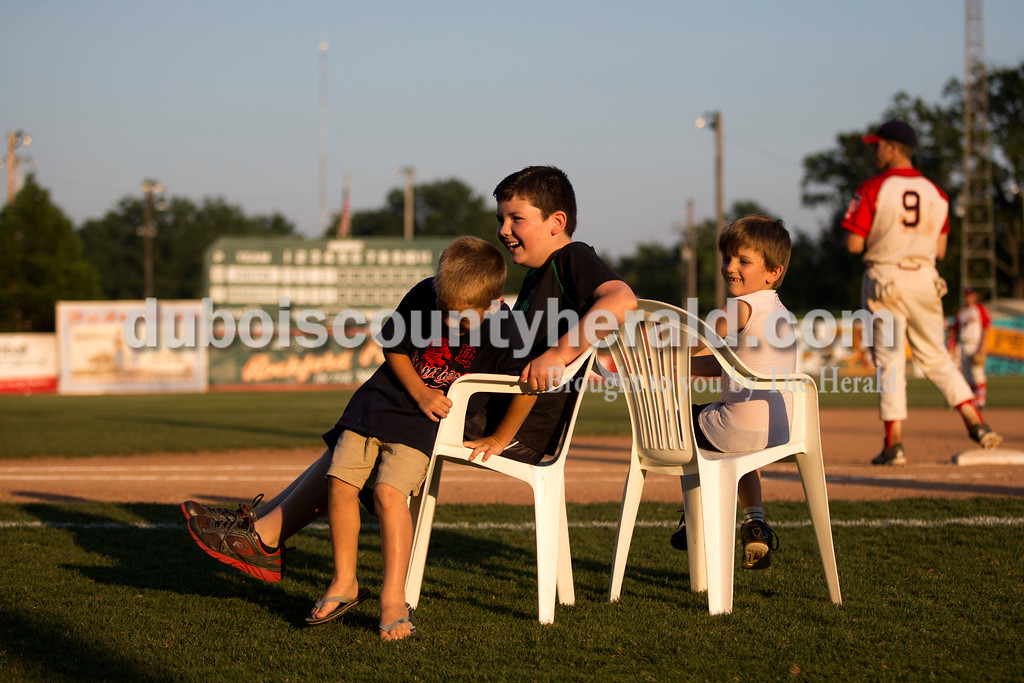 Luke Trout of Holland, 12, laughed as Clint Wirthwein of Huntingburg, 6, tried to squeeze into the seat with him during musical chairs at Wednesday night's Dubois County Bombers game in Huntingburg. Parker Joeppner of Stendal, 5, sat on the chair behind them. <br /> <br /> Alisha Jucevic/The Herald