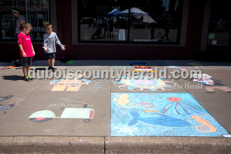 Ariana van den Akker/The Herald<br /> Marisa Carie of Huntingburg, 11, and her brother Aidan admired some of the chalk drawings during the 12th annual Chalk Walk Arts festival in downtown Jasper on Saturday.