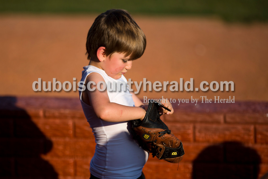 Parker Joeppner of Stendal, 5, played with a baseball mitt during Wednesday night's Dubois County Bombers game against the Fulton Railroaders at League Stadium in Huntingburg. The Bombers won 8-1. <br /> <br /> Alisha Jucevic/The Herald