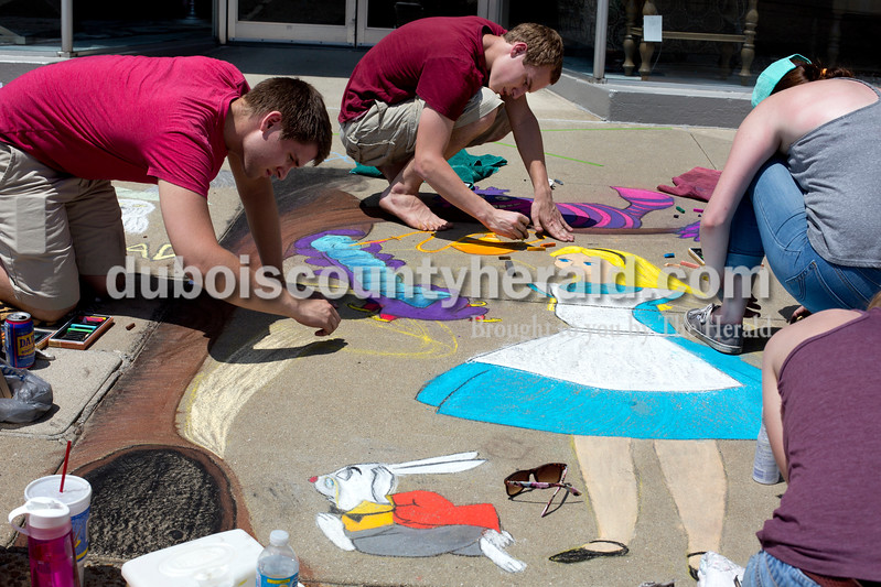 "Ariana van den Akker/The Herald<br /> Cody House of Geneva, Ill. left, and Jared Matsel and Miranda Buffington, both of Jasper, worked on a drawing from ""Alice and Wonderland"" during the 12th annual Chalk Walk Arts festival in downtown Jasper on Saturday."