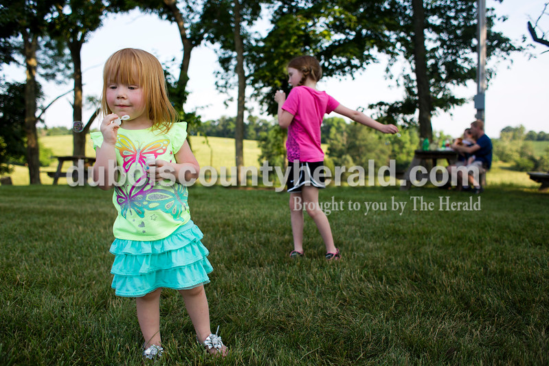 Tessa Guillaume of Apalona, 3, and her sister Summer, 7, blew bubbles in the meadow during the St. Boniface Catholic Parish 150th anniversary celebration on Friday evening in Fulda. The weekend celebration festivities included live music, specialty food, children's games and a beer garden. <br /> <br /> Alisha Jucevic/The Herald