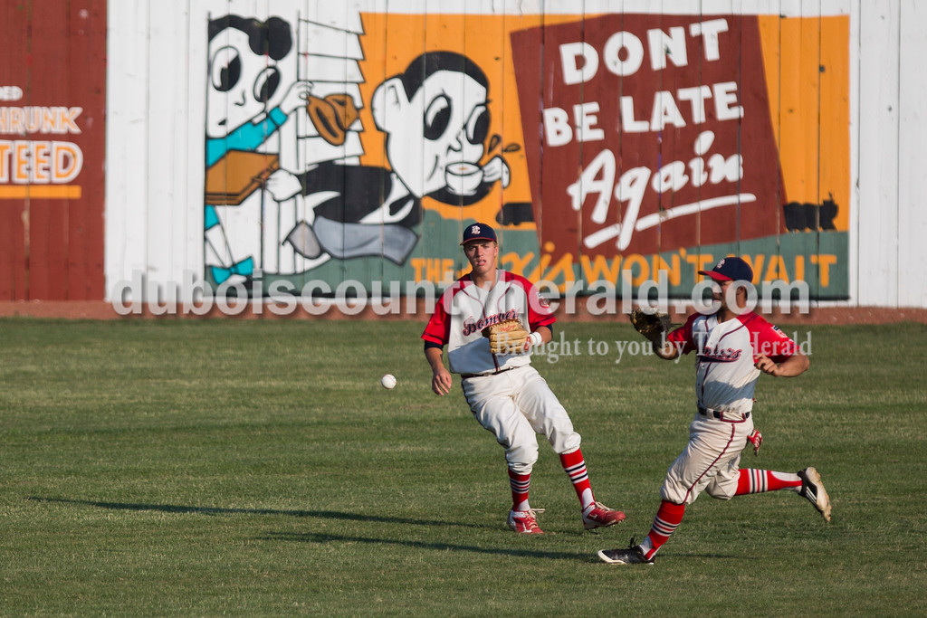 Dubois County Bombers' Drake McNamara, left, and Nicholas Barrientos ran to catch the ball during Wednesday night's game against the Fulton Railroaders at League Stadium in Huntingburg. The Bombers won 8-1. <br /> <br /> Alisha Jucevic/The Herald