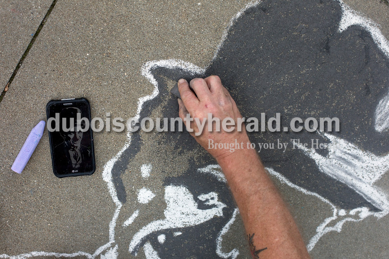 Ariana van den Akker/The Herald<br /> Michael Coles of Jasper worked on a drawing of Charlie Chaplin based on an etching he had done, pictured on his phone, during the 12th annual Chalk Walk Arts festival in downtown Jasper on Saturday.
