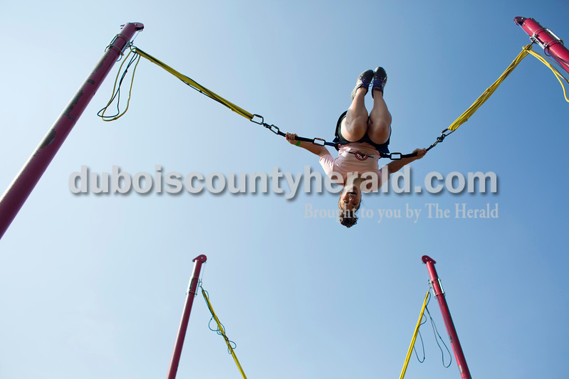 Kyla Gogel of Fulda twirled in a backflip on the trampoline bungee harness attraction at the St. Boniface Catholic Parish 150th anniversary celebration on Friday evening in Fulda. The weekend celebration festivities included live music, specialty food, children's games and a beer garden. <br /> <br /> Alisha Jucevic/The Herald