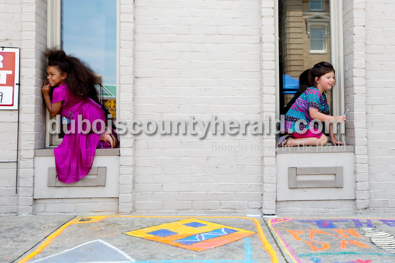 Ariana van den Akker/The Herald<br /> Aanias Jackson, 6, left, and her friend Nevaeh Benton, 4, both of Jasper, giggled while playing a game in which Aanias's mom April (not pictured) had to guess which window the girls were in during the 12th annual Chalk Walk Arts festival in downtown Jasper on Saturday.