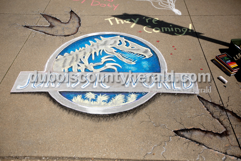 "Ariana van den Akker/The Herald<br /> Marty Vaught of Jasper drew the ""Jurassic World"" logo during the 12th annual Chalk Walk Arts festival in downtown Jasper on Saturday."
