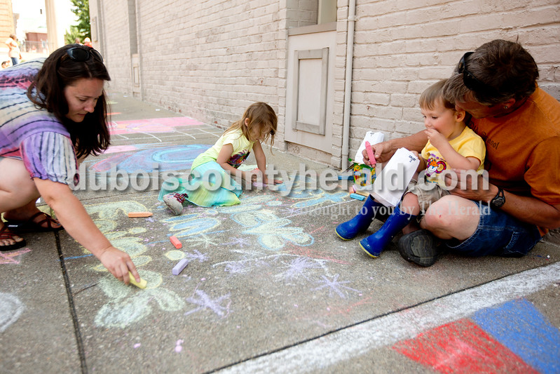 Ariana van den Akker/The Herald<br /> Sherri Uebelhor of Jasper, left, her daughter Mya, 6, son Gavin, 2, and husband Kurt worked on their square during the 12th annual Chalk Walk Arts festival in downtown Jasper on Saturday.