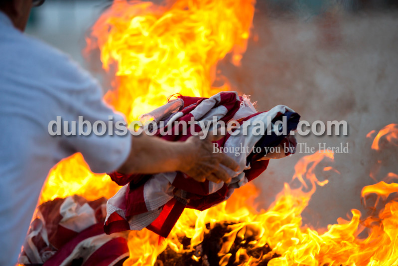 American Legion Post 343 member Steve Hunter of Holland, threw flags on the fire during an official flag burning ceremony Friday evening at  4-H Fairgrounds in Jasper. <br /> Alisha Jucevic/The Herald