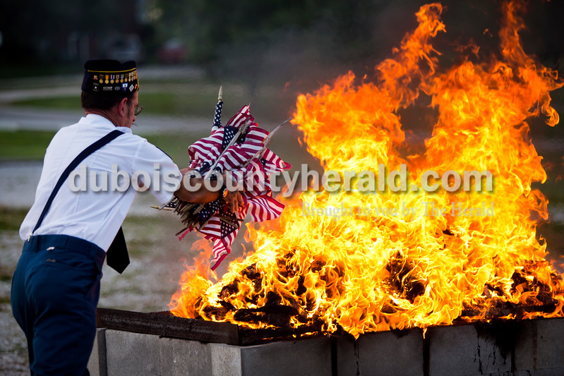 American Legion Post 343 veteran Richard Mangel of Holland threw a handful of small flags on the fire during an official flag burning ceremony Friday evening at  4-H Fairgrounds in Jasper.<br /> <br /> Alisha Jucevic/The Herald