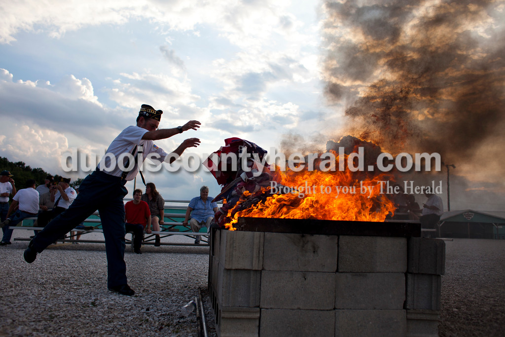 American Legion Post 343 veteran Richard Mangel of Holland threw flags on the fire during an official flag burning ceremony Friday evening at  4-H Fairgrounds in Jasper.<br /> <br /> Alisha Jucevic/The Herald