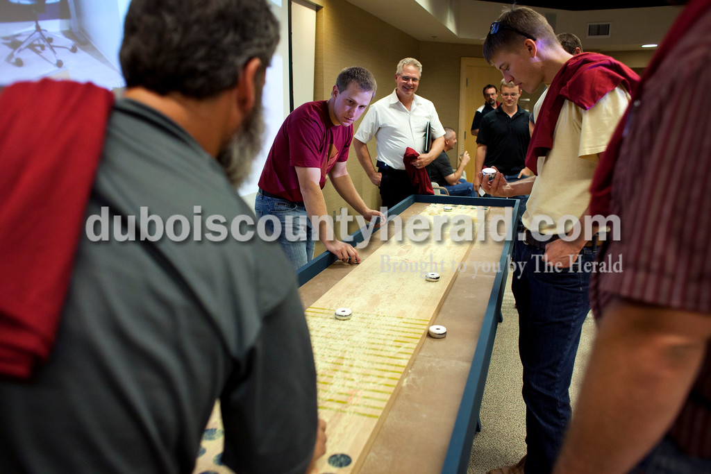 Lance Buechler of Ferdinand, Wayne Mehringer of Dubois, Andrew Kieffner of Jasper and Blake Gogel of Huntingburg watched as Stu Bettag played with the new shuffleboard during the OFS NeoCon reveal party at the company headquarters in Huntingburg. NeoCon is North America's largest exposition and conference for the interior design profession, and OFS decided to bring the neocon experience back to the Huntingburg headquarters to show for the associates a sampling of the company's new products. <br /> <br /> Alisha Jucevic/The Herald