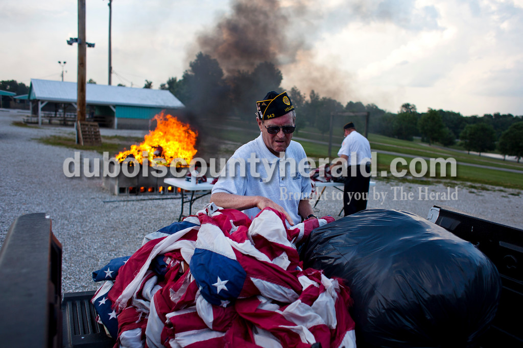 American Legion Post 343 member Steve Hunter of Holland, emptied trash bags stuffed with old flags during an official flag burning ceremony at  4-H Fairgrounds in Jasper. Over 1,000 flags were burning during the ceremony. If you have old flags that you need to dispose of, you can drop them off at any of the American Legion or Veterans of Foreign Wars posts in Dubois County and they will properly dispose of them at the annual ceremony. <br /> <br /> Alisha Jucevic/The Herald