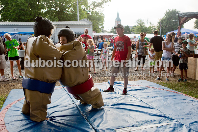 Ellie Hasenour of Holland, 12, left, and her brother Michael bumped bellies as they sumo wrestled each other as Aaron Lubbehusen of St. Henry, 16, refereed during the Heinrichsdorf's Fest in St. Henry on Friday. Rachel Mummey/The Herald