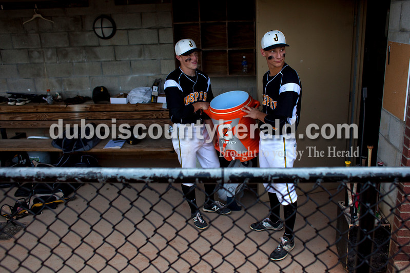 Jasper's Tate Blessinger and Grant Theil looked around the corner of the dugout to find coach Terry Gobert before dumping a bucket of ice water over his head after Saturday's Class 3A semistate championship against West Vigo at Ruxer Field in Jasper. The Wildcats won 6-0. <br /> <br /> Alisha Jucevic/The Herald