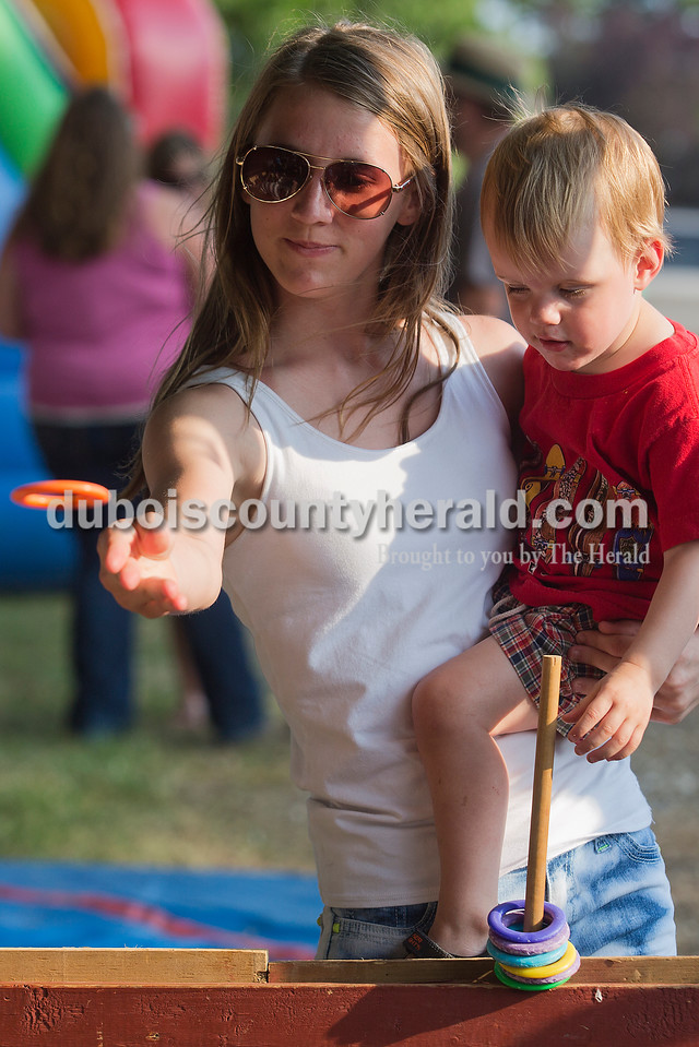 Monica Steckler, 12, held her cousin Rafe Steckler, 1, both of St. Henry at the ring toss booth during the Heinrichsdorf's Fest in St. Henry on Friday. Rachel Mummey/The Herald