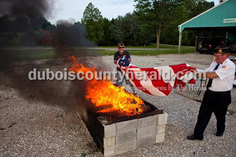 "Veterans of Foreign Wars Post 2366 commander Mark Jackson of Jasper and American Legion Post 343 veteran Bob Hunter of Holland threw a flag onto the fire during an official flag burning ceremony on Friday evening at  4-H Fairgrounds in Jasper. According to the Patriotic Customs section of the U.S. Code, ""The flag, when it is in such condition that it is no longer a fitting emblem for display, should be destroyed in a dignified way, preferably by burning."" Dubois County veterans gathered at the Dubois County 4-H Fairgrounds tonight to respectfully dispose of more than 1,000 American flags.<br /> <br /> Alisha Jucevic/The Herald"