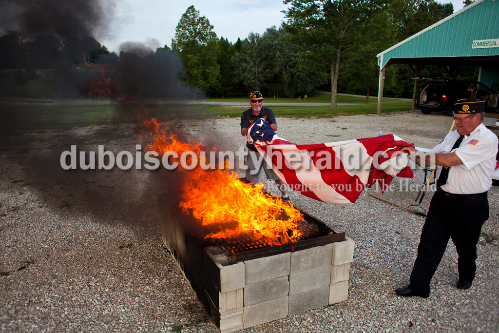 """Veterans of Foreign Wars Post 2366 commander Mark Jackson of Jasper and American Legion Post 343 veteran Bob Hunter of Holland threw a flag onto the fire during an official flag burning ceremony on Friday evening at  4-H Fairgrounds in Jasper. According to the Patriotic Customs section of the U.S. Code, """"The flag, when it is in such condition that it is no longer a fitting emblem for display, should be destroyed in a dignified way, preferably by burning."""" Dubois County veterans gathered at the Dubois County 4-H Fairgrounds tonight to respectfully dispose of more than 1,000 American flags.<br /> <br /> Alisha Jucevic/The Herald"""