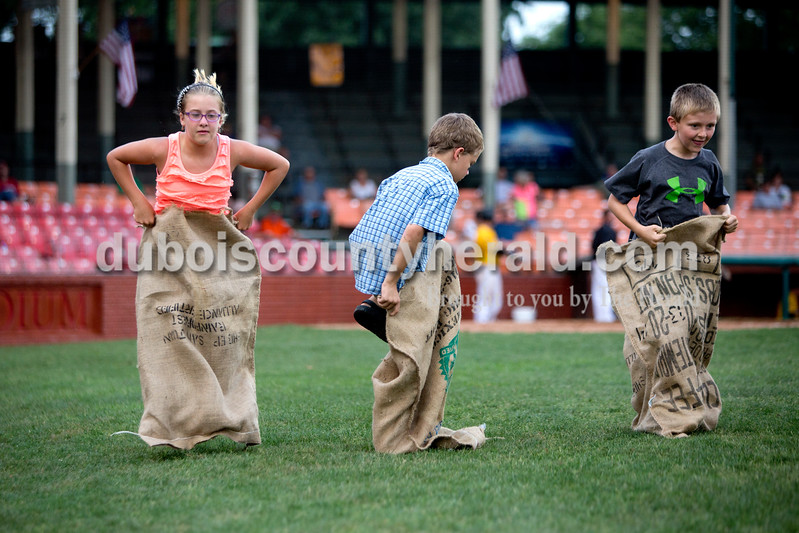 Madelyn Lau of Huntingburg, 11, left, Colton Harris of Jasper, 8, and Lane Reckelhoff of Dale, 8, competed in the potato sack race between innings of Monday night's Bombers game against the Madisonville Miners at League Stadium in Huntingburg. The Bombers won 13-1. Ariana van den Akker/The Herald