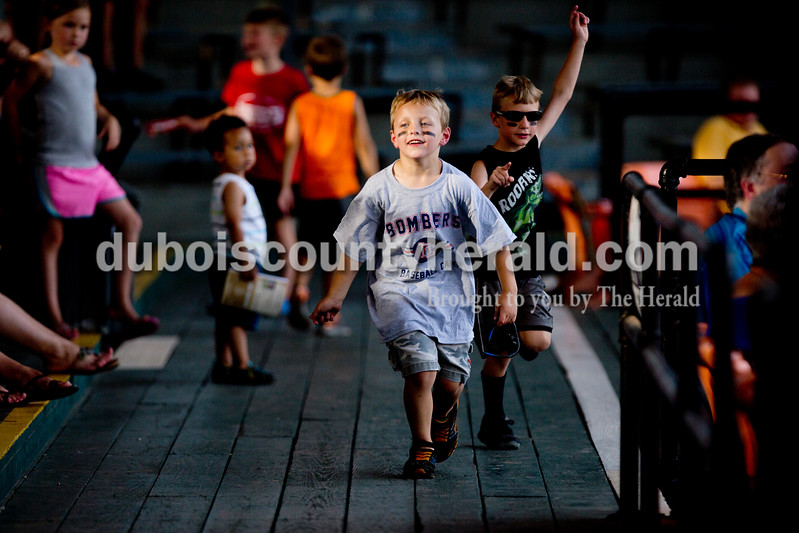 Wyatt Smoker, left, and his friend Logan Kratzer, both 6 and of Huntingburg, dashed around the stands during Monday night's Bombers game against the Madisonville Miners at League Stadium in Huntingburg. The Bombers won 13-1. Ariana van den Akker/The Herald