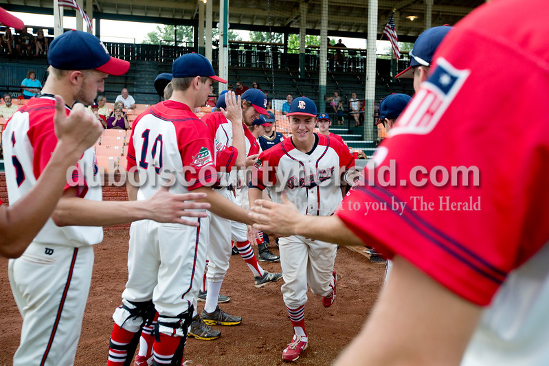 Dubois County's Drake McNamara was greeted by his teammates before Monday night's Bombers game against the Madisonville Miners at League Stadium in Huntingburg. The Bombers won 13-1. Ariana van den Akker/The Herald