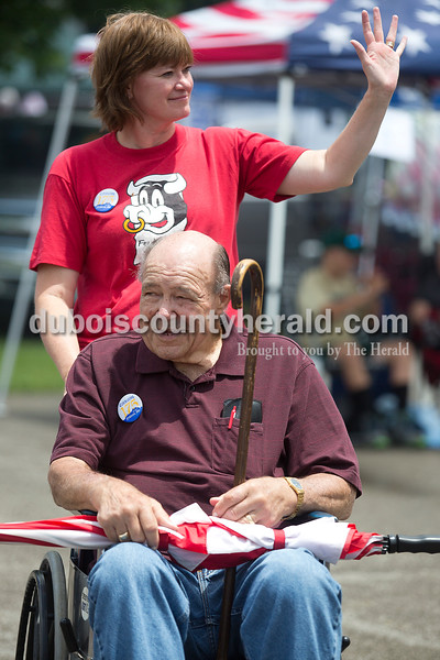 """Donna Lueken of Ferdinand waived to a friend while pushing her dad Bernie Pund of Ferdinand around the Backyard BBQ contest at 18th St. Park during the Ferdinand 175th Celebration on Saturday. Pund was in charge of the parade in 1990. """"As long as I've got my pusher, I get around find,"""" Pund said. Rachel Mummey/The Herald"""