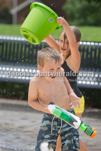 Cohen Robb, 5, dodged a bucket of water held by Mya Neighbors, 6, both of Jasper, as they played in the water fountain at Central Green next to the Cabby O'Neill Gymnasium in Jasper on Monday. Rachel Mummey/The Herald
