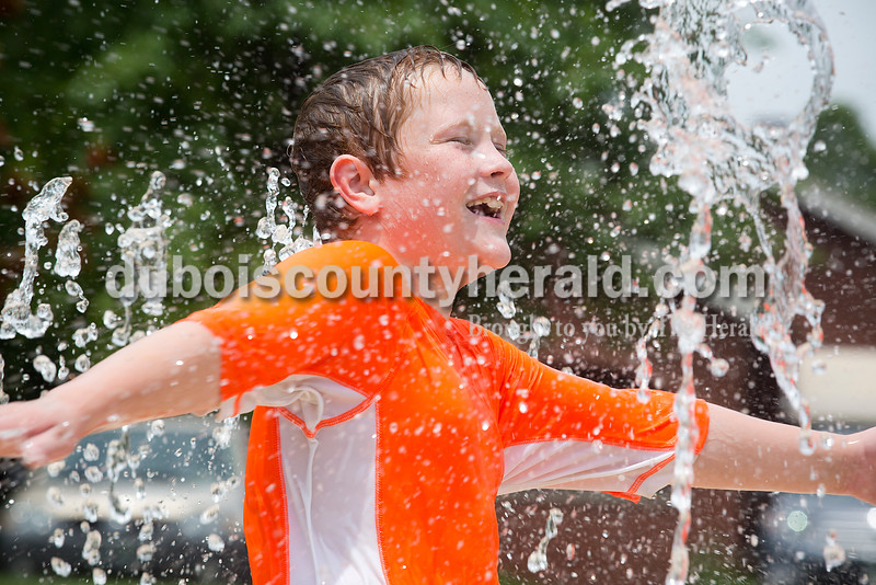 Aaron Bayer of Jasper, 9, ran through the water fountain at Central Green next to the Cabby O'Neill Gymnasium in Jasper on Monday. Bayer was there with his sister Jasmine, 18, who was babysitting for Mya Neighbors of Jasper, 6, and her brother Ty, 11. Rachel Mummey/The Herald