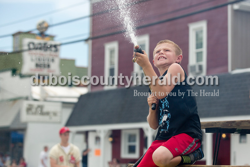 Blake Taylor of St. Henry sprayed the audience from the Volunteer Fire Department's float during the parade for the Ferdinand 175th Celebration on Sunday. Rachel Mummey/The Herald