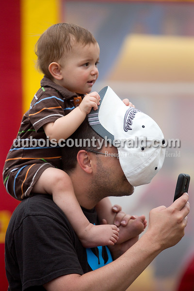 One-year-old Alex Johnson of Monticello, Ind., covered his dad Keith's face as he tried to take a picture with his cell phone while perusing the game booths at 18th St. Park during the Ferdinand 175th Celebration on Saturday. Johnson's in-laws are Ed and Ursula Cole of Jasper and they were visiting for the celebration. Rachel Mummey/The Herald