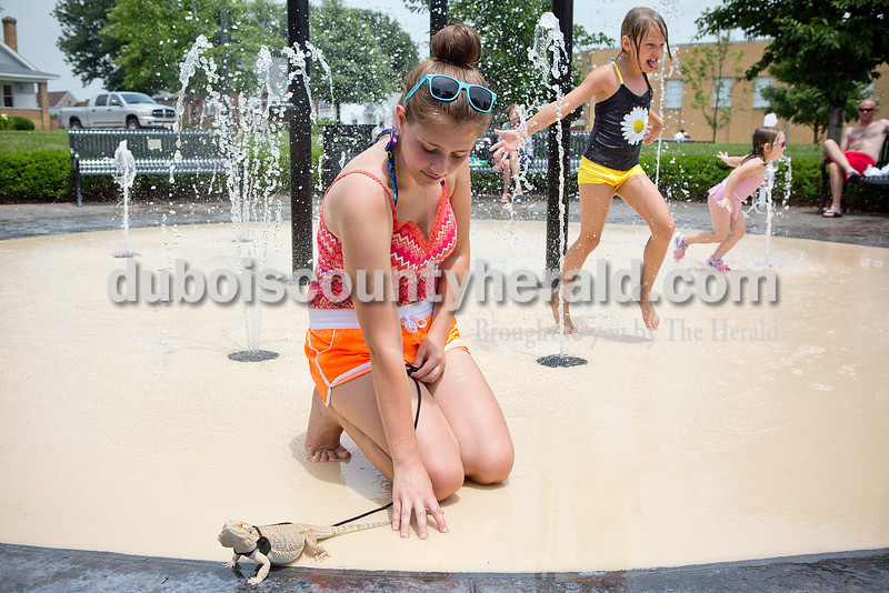 Jasmine Bayer of Jasper, 18, let her pet bearded dragon Lily get her feet wet while Mya Neighbors, 6, and Marissa Wolf, 3, both of Jasper, ran through the water fountain at Central Green next to the Cabby O'Neill Gymnasium in Jasper on Monday. Bayer said she likes taking her pet lizard out during the summer time because she loves the sun and the warm climate. Rachel Mummey/The Herald