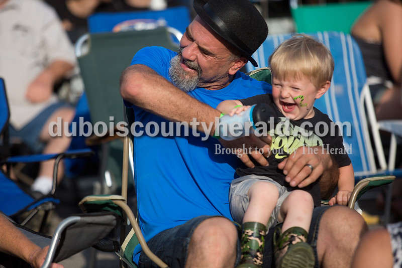 Stu Zink tickled his great-nephew Bently Mohr, 2, both of Ferdinand, while he played the air guitar during the performance by The Georgia Satellites at 18th St. Park during the Ferdinand 175th Celebration on Saturday. Rachel Mummey/The Herald
