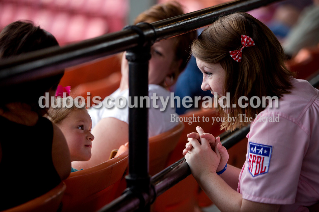 Rockford Peach Gabbi Skaggs of Ireland asked Keira Schurz of Jasper, 3, if she wanted eye black during Monday night's Bombers game against the Madisonville Miners at League Stadium in Huntingburg. The Bombers won 13-1. Ariana van den Akker/The Herald