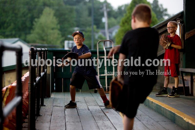 Josh Gardiner, left, caught a ball thrown by his friend Spencer Stevens, both 8 and of Loogootee, as Malaki Downen of Vincennes, 8, waited for his turn to catch during Monday night's Bombers game against the Madisonville Miners at League Stadium in Huntingburg. The Bombers won 13-1. Ariana van den Akker/The Herald