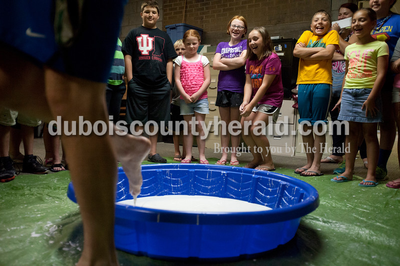 Erica Lafser/The Herald<br /> Bellarmine student and Bombers player Brady Pfaadt demonstrated how to run across the kid sized pool filled with the children's oobleck both slowly and quickly. When Pfaadt went slowly he began to sink into the substance, but when Pfaadt went quickly his feet were clean. This took place at the STEAM! program at the Huntingburg Public Library on Wednesday. The oobleck activity consisted of mixing one and a half cups of cornstarch with one cup of water together. It taught the kids about the properties of oobleck because when you play with the substance slowly it is liquid, but if you play with it quickly it can turn into a solid form, similar to quicksand. They put this in a pool so kids could run across the substance without having anything on their feet, but if they went too slow the kid's feet would start to sink. STEAM! is a five-week program for ages 8 and older that will make science, technology, engineering, art and math fun.