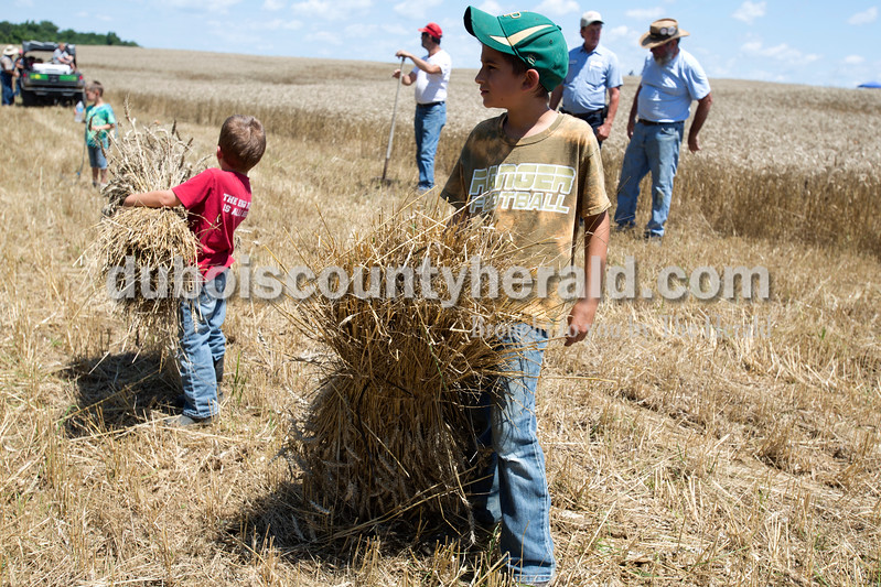 Erica Lafser/The Herald<br /> Keegan Betz of Schnellville, 5, right stood with his older brother Conner Betz of Schnellville, 8, while they waited to put the bundles of wheat they held onto a wagon during the Schnellville Sesquicentennial wheat threshing on Sunday at the field outside of the Schnellville Community Club. This event occurs every 25 years.