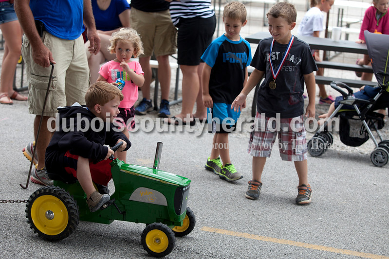 Erica Lafser/The Herald<br /> Mason Schmidt of Jasper, 6, competed in the kid's tractor pull event on Saturday at the Celestine Streetfest. This is a yearly town festival that occurs on the last Saturday in June. Mason was cheered on by Elin Sermersheim of Celestine, 3, center left, and Elin's brother Kolton Sermersheim of Celestine, 5, center right, and Mason's brother Kaiden Schmidt of Jasper, 7, far right.