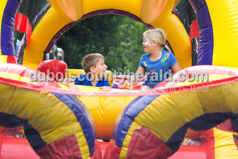 Erica Lafser/The Herald<br /> Cameron Tooley of Huntingburg, 10, left, and his sister Mallory Tooley of Huntingburg, 8, right, shared a laugh during one of the inflatable courses for the kids at the Celestine Streetfest on Saturday. This is a yearly town festival that occurs on the last Saturday in June.
