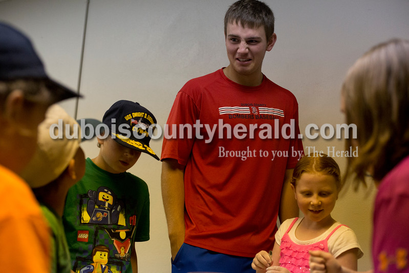 "Erica Lafser/The Herald<br /> Bellarmine student and Bombers player Brady Pfaadt of Louisville, Kentucky had fun with the kids participating in the STEAM! program at the Huntingburg Public Library on Wednesday. The Bombers have made about 12 public appearances like this at day cares, youth programs and will appear at a nursing home in a couple of weeks. The oobleck activity was the first ""crafty"" activity the Bombers helped with; they usually assist with activities such as kickball or other sports. The oobleck activity consisted of mixing one and a half cups of cornstarch with one cup of water together. It taught the kids about the properties of oobleck because when you play with the substance slowly it is liquid, but if you play with it quickly it can turn into a solid form. STEAM! is a five-week program for ages 8 and older that will make science, technology, engineering, art and math fun."