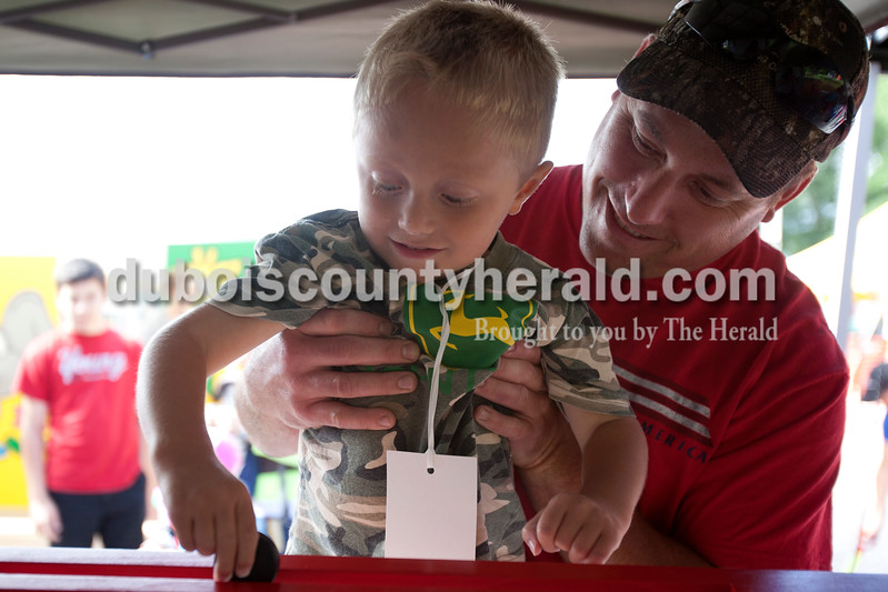 Erica Lafser/The Herald<br /> Drake Lindauer of Celestine, 3, played a game at the Celestine Streetfest on Saturday with the help of his father Andy Lindauer of Celestine. This is a yearly town festival that occurs on the last Saturday in June.