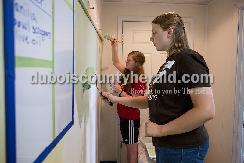 Hannah Soellner of Jasper, 16, left, and Taylor Blalock of Ferdinand, 16, painted walls at the Community Meal Kitchen at St. Vincent de Paul as part of service project in conjunction with Rock Your Faith in Jasper on Tuesday. Rachel Mummey/The Herald