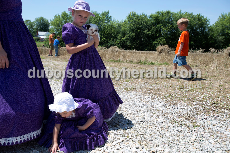 Erica Lafser/The Herald<br /> Ava Verkamp of Schnellville, 7, standing, held her family dog, Roscoe, 10 weeks, while her sister Sophia Verkamp, 2, played in the rocks during the Schnellville Sesquicentennial wheat threshing on Sunday at the field outside of the Schnellville Community Club. This event occurs every 25 years.