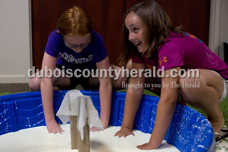 Erica Lafser/The Herald<br /> Huntingburg Elementary student Ana Hewitt of Huntingburg, 11, left, played in the oobleck pool with Jasper Elementary student Ellie Knies of Huntingburg, 9, right, during the STEAM! oobleck activity on Wednesday at the Huntingburg Public Library. The oobleck activity consisted of mixing one and a half cups of cornstarch with one cup of water together. It taught the kids about the properties of oobleck because when you play with the substance slowly it is liquid, but if you play with it quickly it can turn into a solid form, similar to quicksand. STEAM! is a five-week program for ages 8 and older that will make science, technology, engineering, art and math fun.