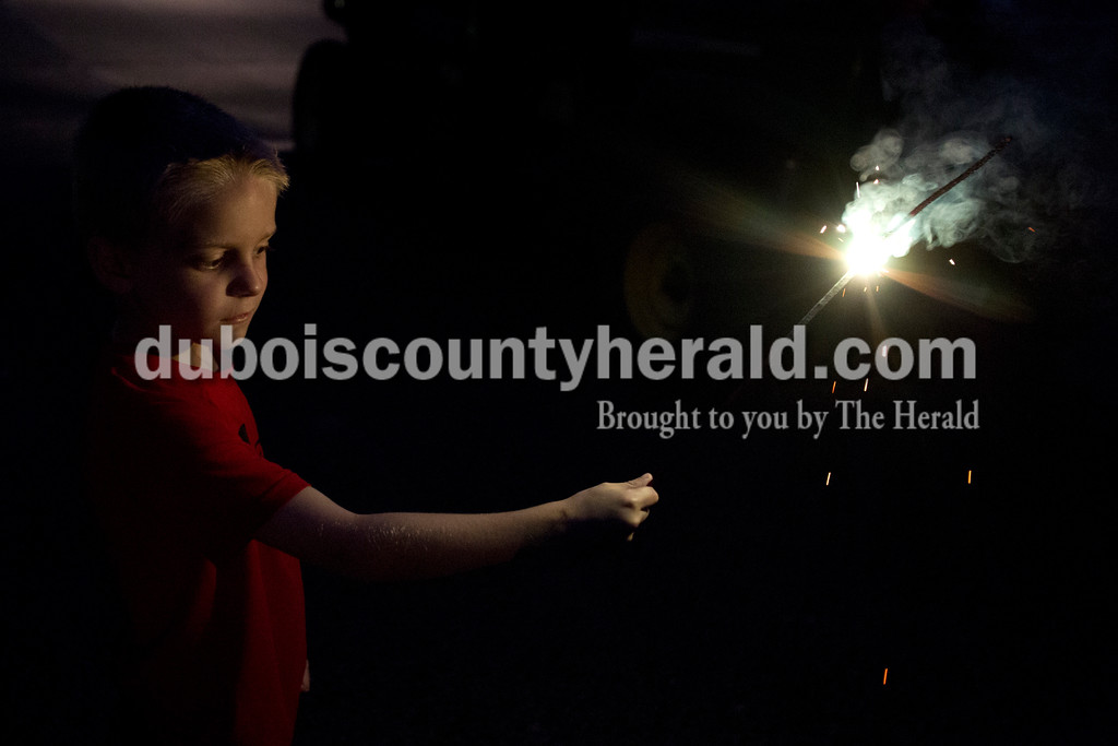 Erica Lafser/The Herald<br /> Kolten Dewitt of Huntingburg, 8, looked down with dissappointment after he was told by lake officials that fireworks were not allowed on Saturday evening at Patoka Lake for Thunder over Patoka. Since the beach at Patoka Lake flooded, everyone was relocated to a higher parking lot.