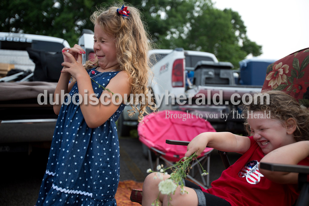 Erica Lafser/The Herald<br /> Aryssa Schipp of Jasper, 5, left, reacted to flowers being thrown in her face with her friend Lexus Griffith of Dubois, 3, right, on Saturday evening at Patoka Lake while they waited for Thunder Over Patoka. Since the beach at Patoka Lake flooded, everyone was relocated to a higher parking lot.