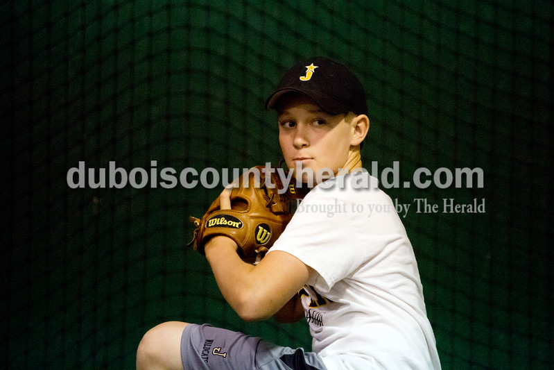 Ariana van den Akker/The Herald<br /> Grant Ahlbrand of Jasper, 14, wound up to pitch during baseball practice at the field house at Ruxer Field in Jasper on Thursday evening.