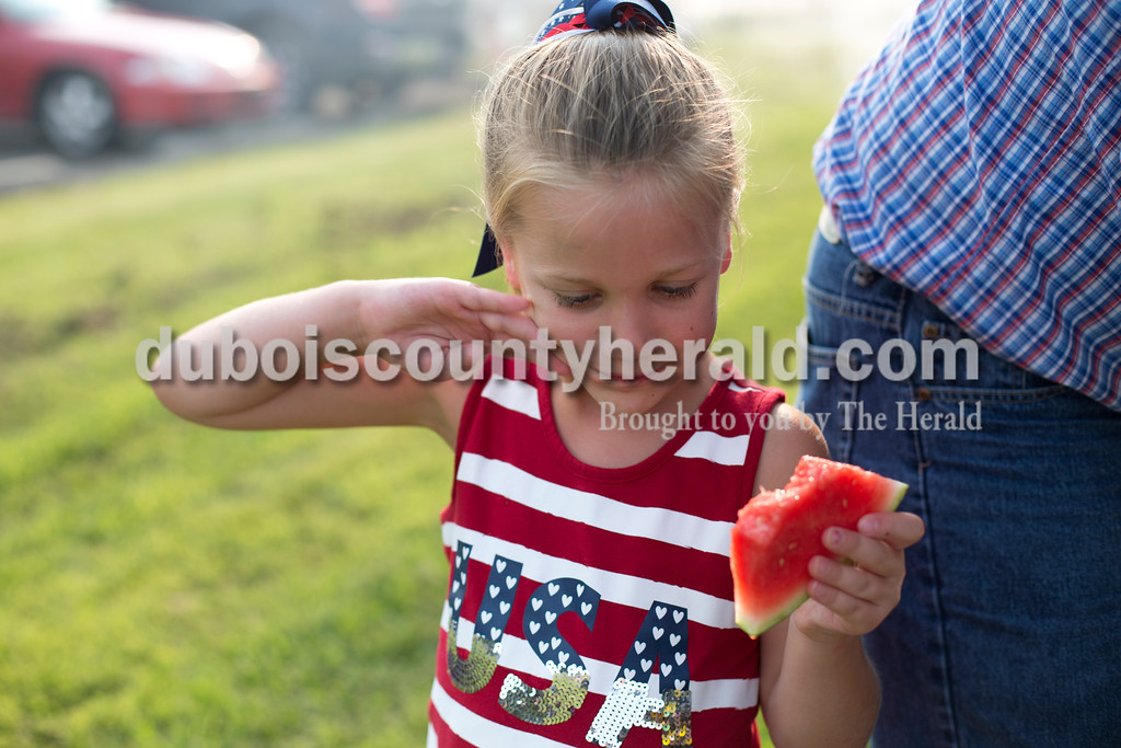 Erica Lafser/The Herald<br /> Aubrey Ashwill of Veedersburg, 6, wiped the watermelon juice off of her face on Saturday evening at Patoka Lake for Thunder Over Patoka. Since the beach at Patoka Lake flooded, everyone was relocated to a higher parking lot.